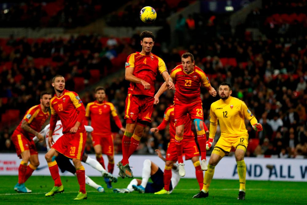 Montenegro's Nikola Vukcevic (centre) jumps to head the ball clear.