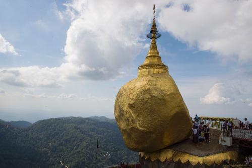 Devotees pray before a huge rock covered with layers of gold at Kyaiktiyo pagoda on Mount Kyaiktiyo.