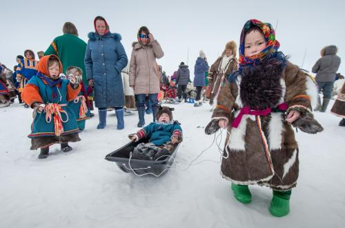 Children play on the snow as people watch a reindeer race on Reindeer Herders Day yesterday in the Yamalo-Nenets region of Russia