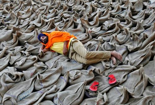 A farmer rests upon sacks at a wholesale grain market