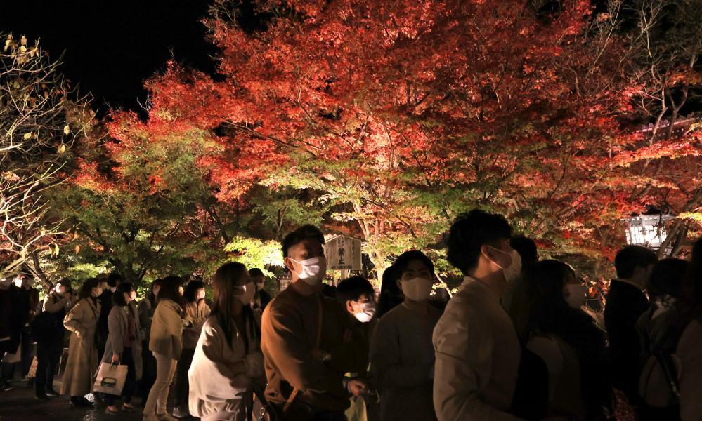 People enjoy illuminated autumn leaves at the Eikando temple in Kyoto on Saturday, 21 November 2020.