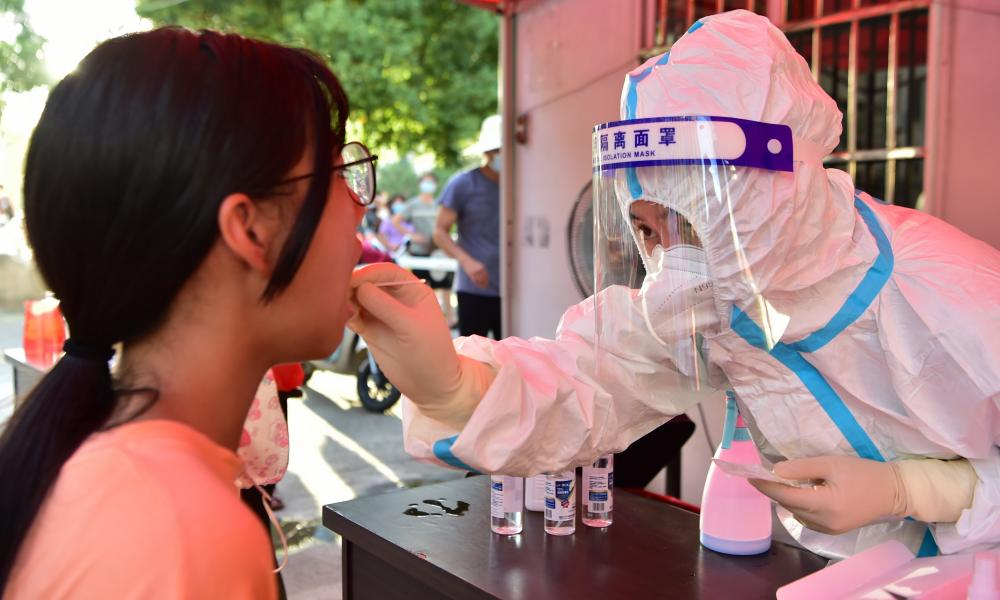 A health worker collects swab sample from a resident for Covid-19 test in China's Fujian Province