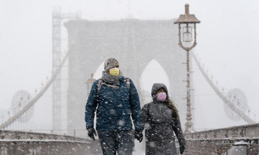 A couple wearing masks walk on the Brooklyn Bridge in New York City, as a winter snowstorm walloped the eastern US on Monday.