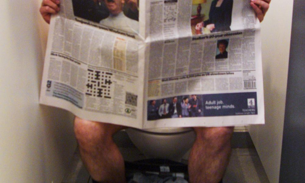 A man reading a newspaper on the toilet