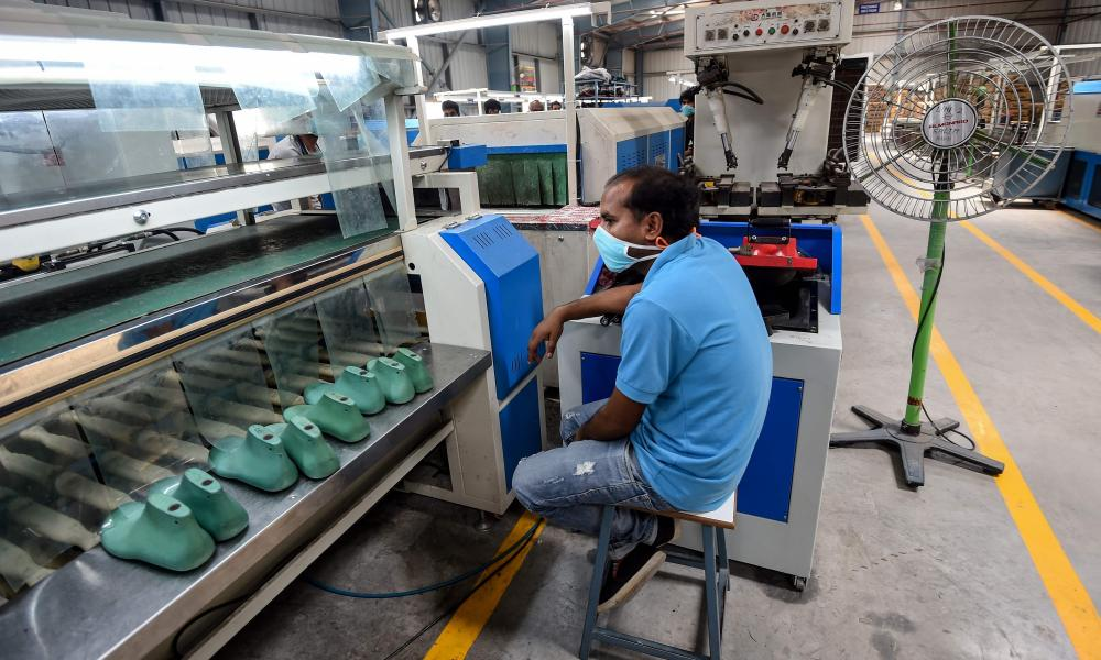 A worker is waiting for products to arrive on a production line at the Aqualite footwear factory in Bahadurgarh in the northern Indian state of Haryana.