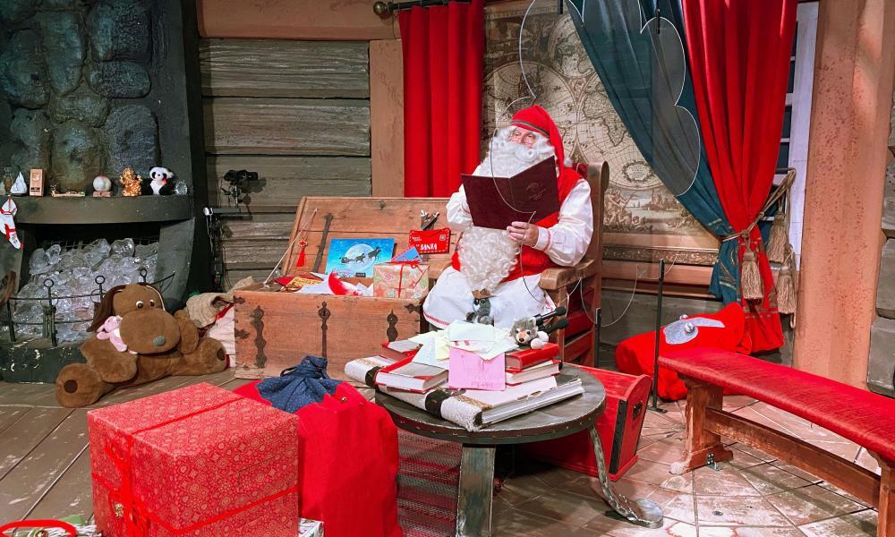 Santa Claus in his chamber behind a plexiglas screen in the village of Rovaniemi, Finland
