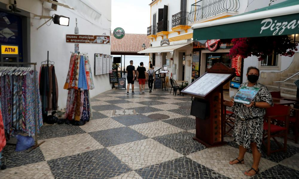 A server offers a menu on a quiet street during the coronavirus pandemic in downtown Albufeira, in the Algarve region of Portugal on Monday.
