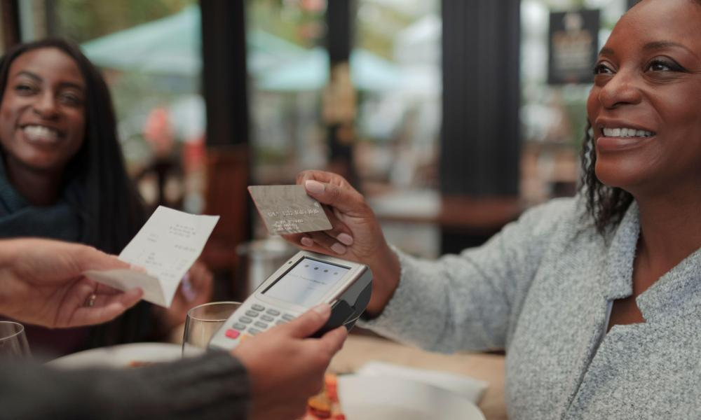 A model image: a customer pays a waiter with a contactless card at cafe.
