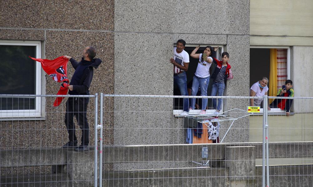Residents of the quarantined high-rise building are standing on windowsills and pursuing a police operation in Goettingen, Germany, Saturday, June 20, 2020. (Stefan Rampfel/dpa via AP)