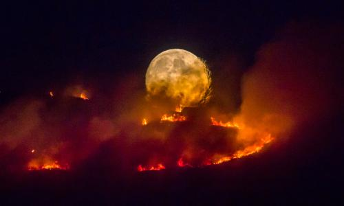 The full moon rises behind burning moorland as a large wildfire sweeps across the moors between Dovestones and Buckton Vale in Stalybridge, Greater Manchester 26th June 2018   The BPPA Exhibition Entry 2019