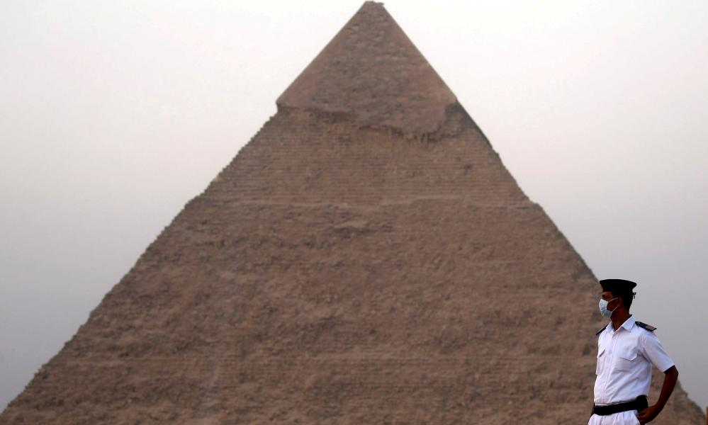 A policeman wearing a protective face mask takes his position, in front of the Pyramid of Khufu in Giza, Egypt.