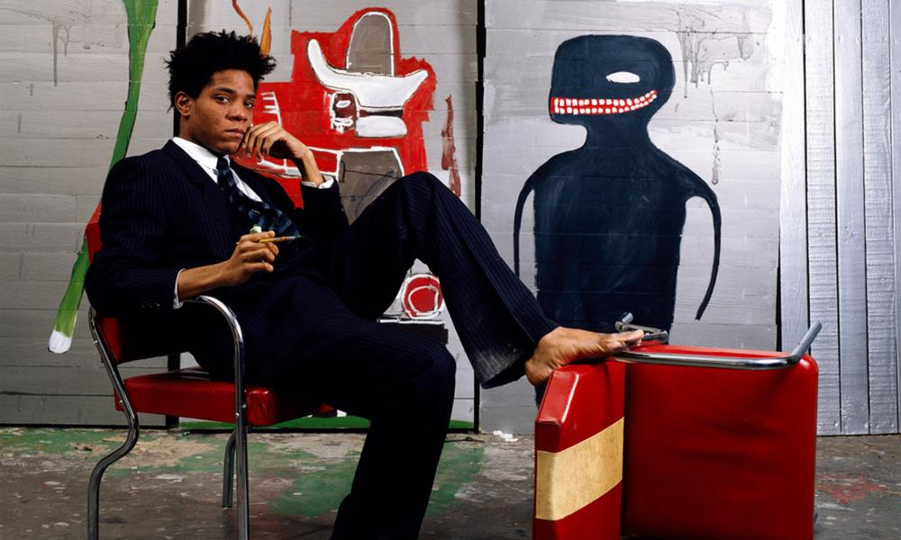 Jean-Michel Basquiat poses with his art in 1985.