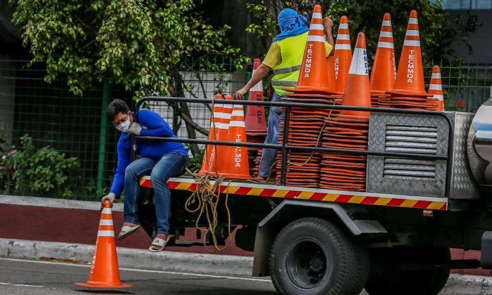 Workers from the Metropolitan Manila Development Authority install traffic cones as they prepare for the rush of commuters due to the easing of the Covid-19 lockdown restrictions in Manila, the Philippines on 31 May, 2020.