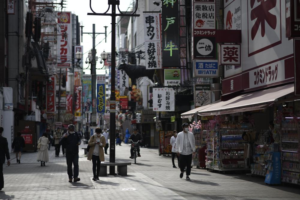 People walk in the entertainment district of Dotonbori in Osaka, Japan