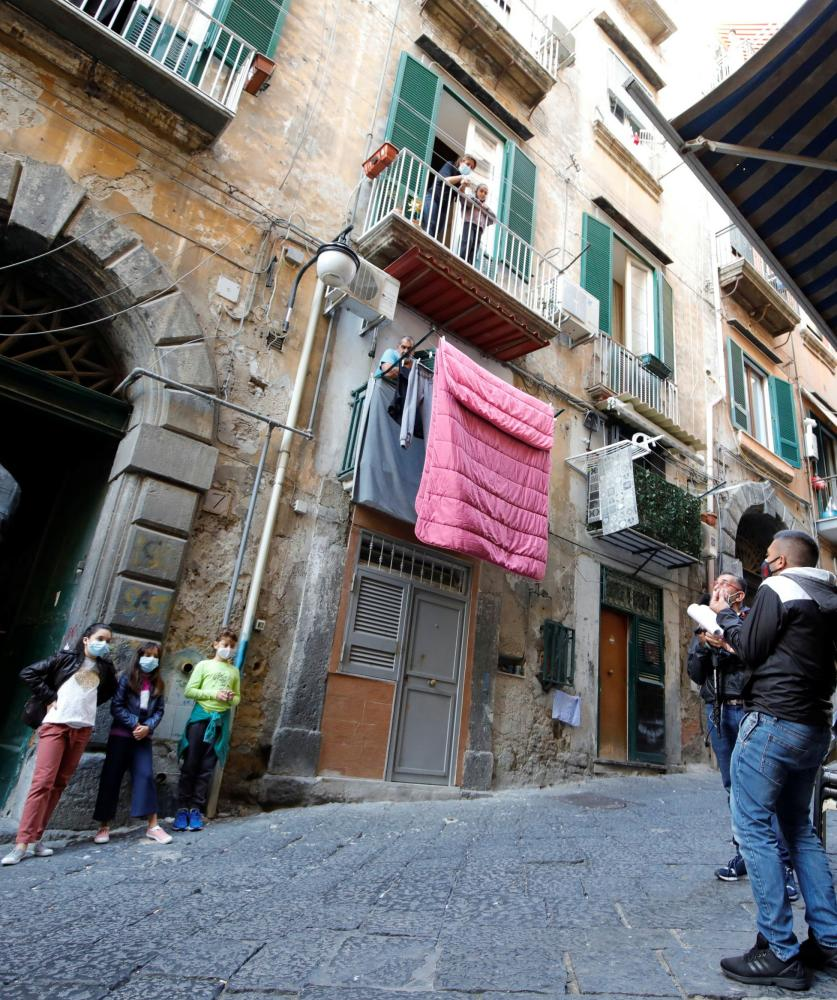 Naples school teacher Tonino Stornaiuolo holds his lessons to students on their balconies while he safely social distances in the street below.