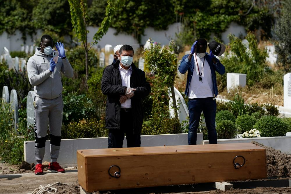 Mourners pray in front of the coffin of a person who died from coronavirus, at the Spanish Muslim military cemetery in Grinon.