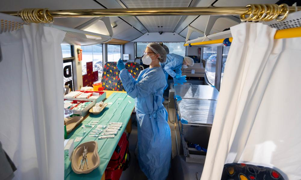 Nurses prepare doses of the Pfizer/BioNTech vaccine at a mobile vaccination centre in a modified bus in Großhartmannsdorf, Germany, in an effort to better reach rural communities