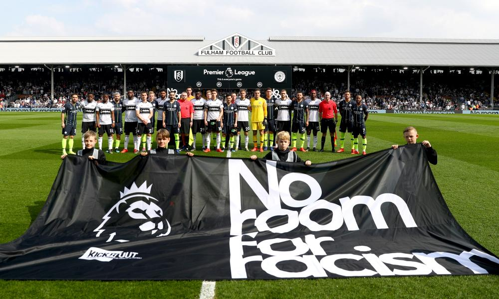 The Fulham and Manchester City players stand with the match officials in protest against racism.