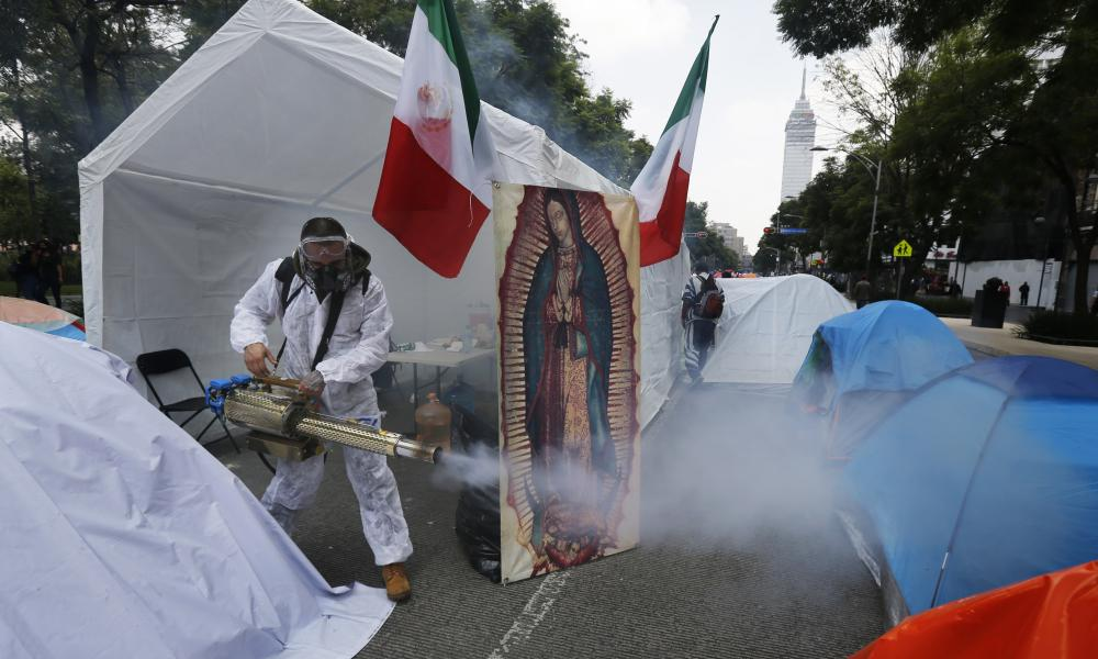 A sanitation technician disinfects tents set up on Mexico City's Juarez Avenue to demand the resignation of Mexican President Andrés Manuel López Obrador, commonly known by his initials AMLO, Tuesday, 22 September, 2020.