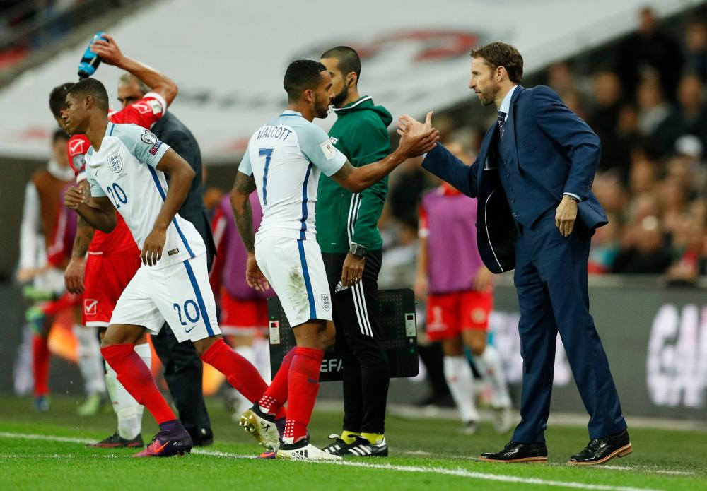Walcott shakes hands with Southgate as Rashford comes on.