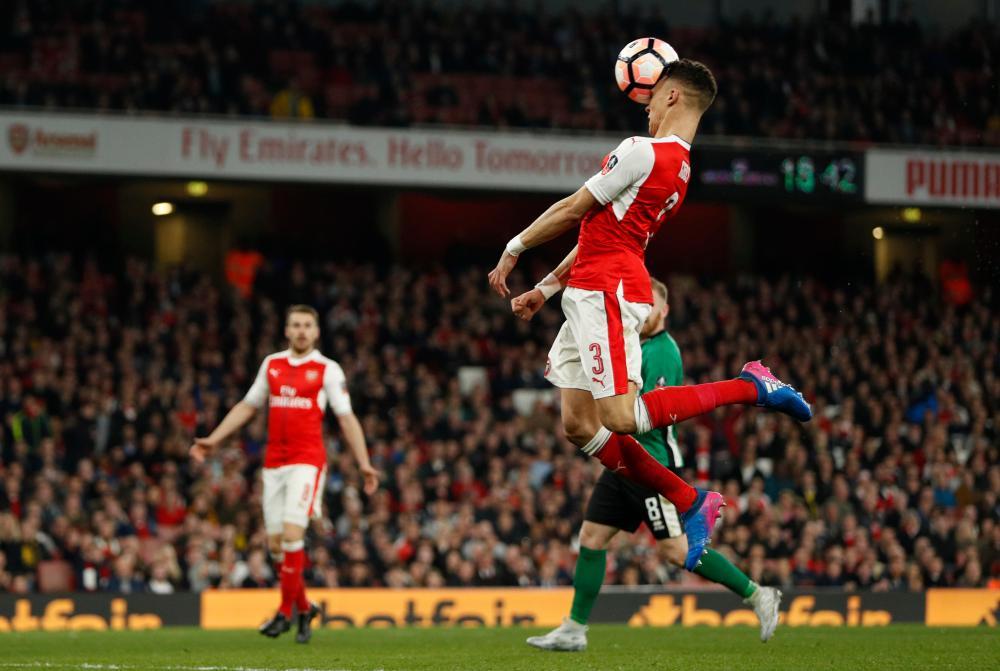 Arsenal's Kieran Gibbs heads the ball over the bar.