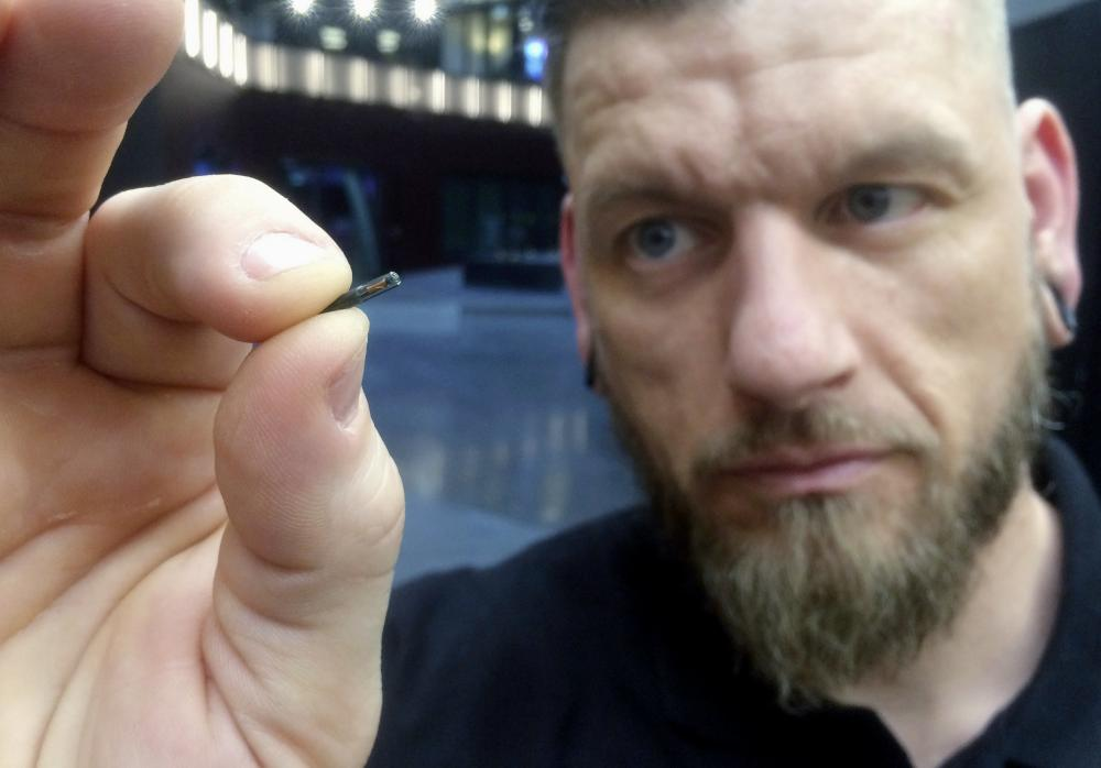 In this March 14, 2017, file photo, Jowan Osterlund from Biohax Sweden, holds a small microchip implant, similar to those implanted into workers at the Epicenter digital innovation business center during a party at the co-working space in central Stockholm. Three Square Market in River Falls, Wis., is partnering with Sweden's BioHax International, offering to microchip its employees, enabling them to open doors, log onto their computers and purchase break room snacks with a simple swipe of the hand.