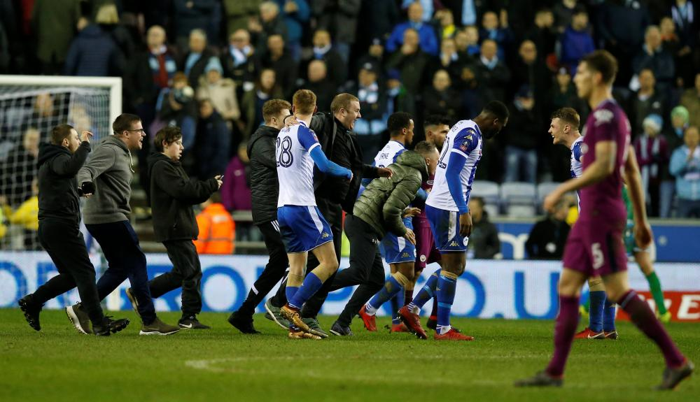 Wigan Athletic's Jay Fulton celebrates with fans on the pitch after the match.
