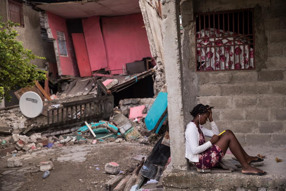 A girl checks her cell phone in front her house destroyed by the 7.2 earthquake in Les Cayes, Haiti