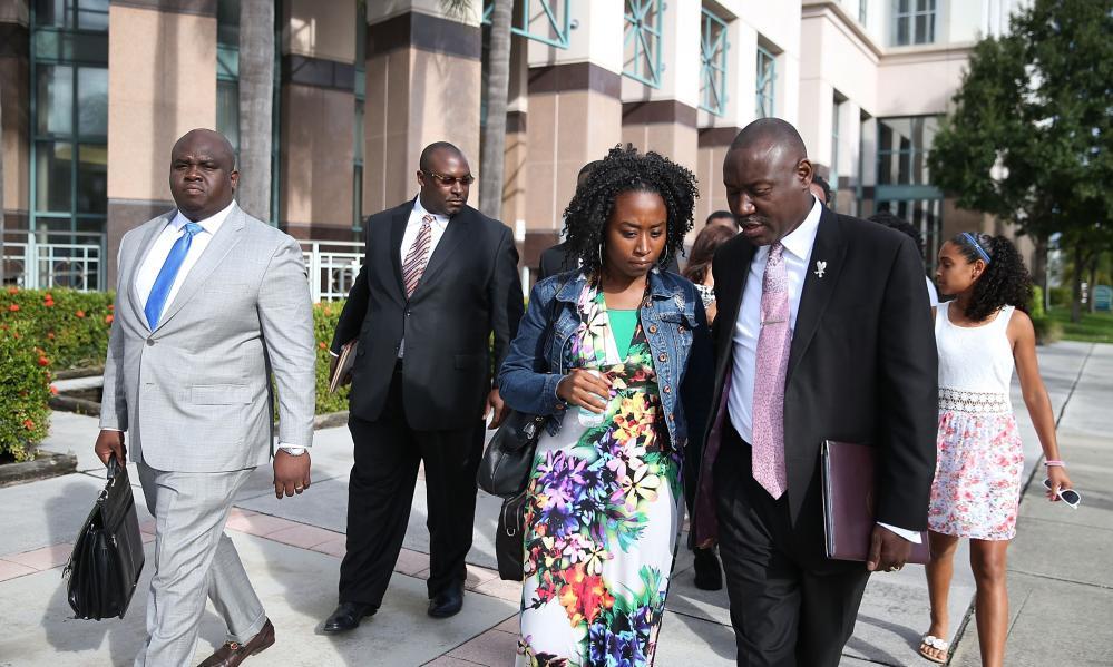 Attorney Benjamin Crump walks with Melissa Jones, sister of Corey Jones, before a media briefing in October 2015.