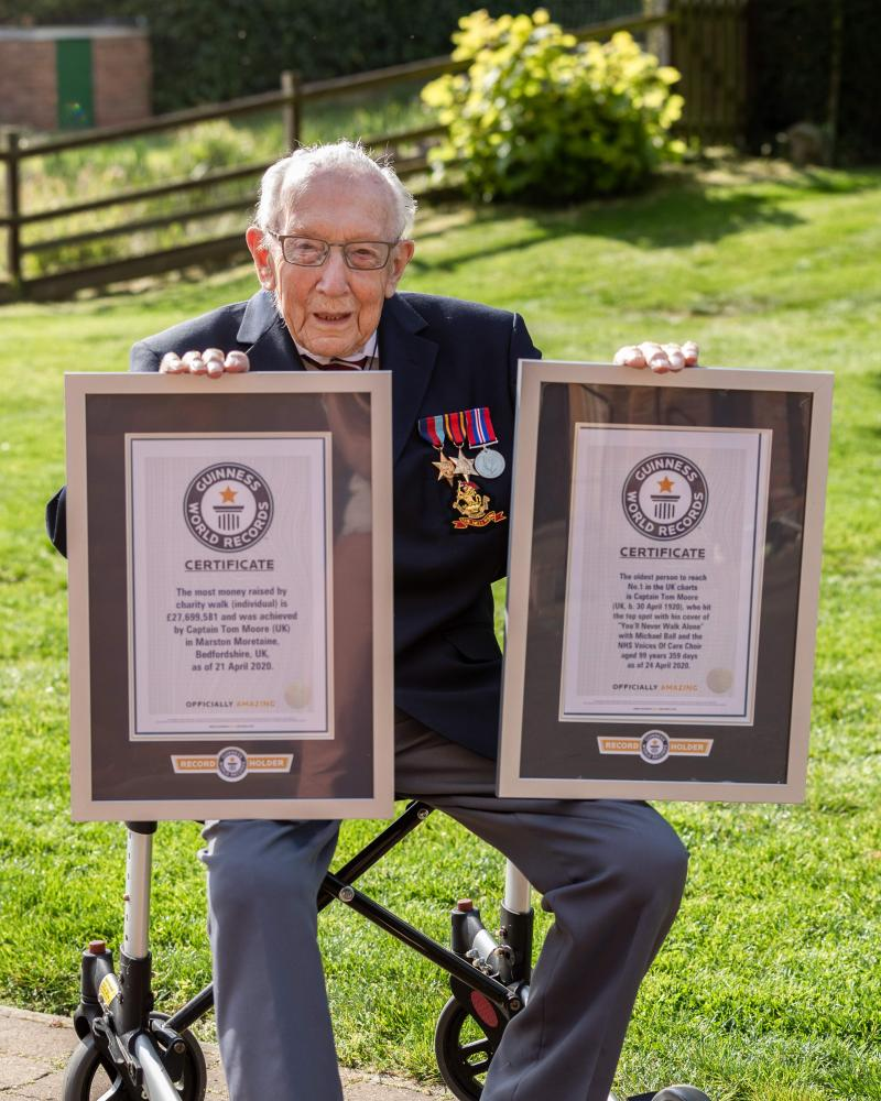 Captain Tom Moore, 99, posing with his two certificates after he broke the record for the most money raised by a charity walk (individual) and at the age of 99 years 359 days became the oldest person to reach number one in the UK charts.