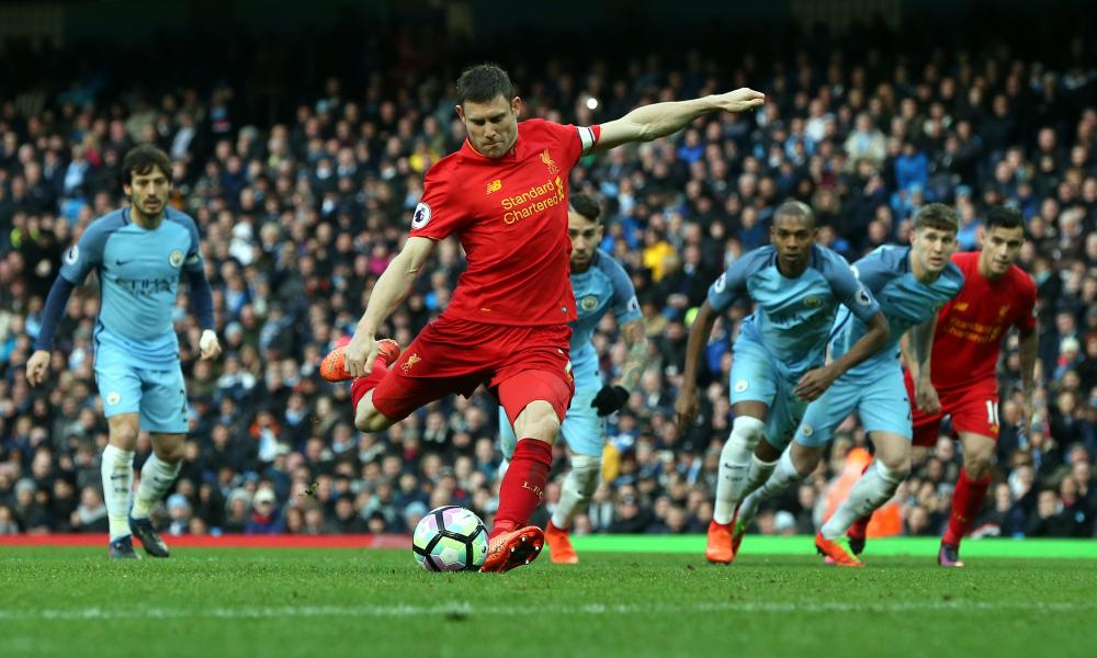 Liverpool's James Milner (C) shoots to score a penalty during the English Premier League soccer match between Manchester City and Liverpooll at the Etihad Stadium, Manchester