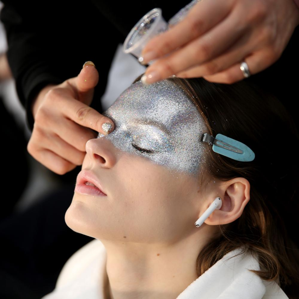 The makeup artist Pat McGrath covered the top half of the faces of several models with silver glitter