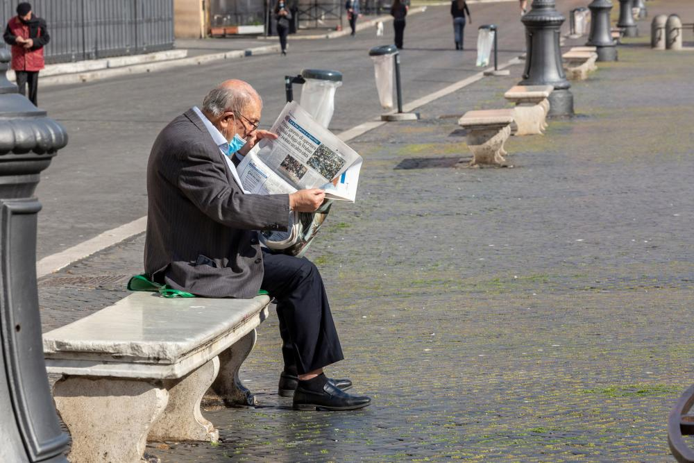 A man sits on a bench in the Piazza Navona, in Rome, and reads the newspaper