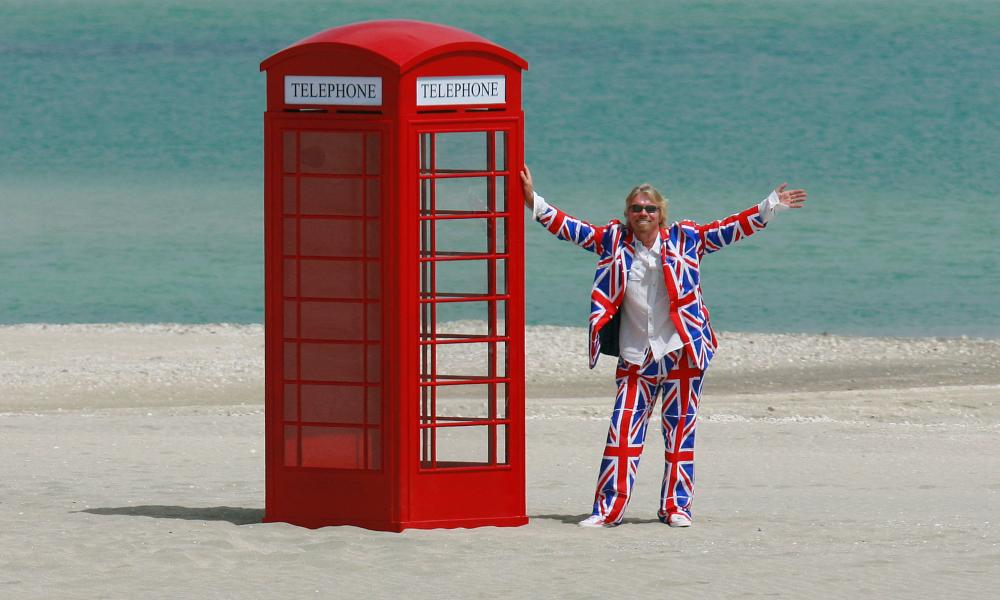 Sir Richard Branson poses with a red telephone box on Britain.