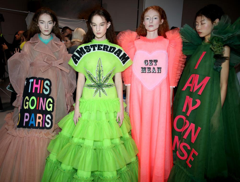 Models in slogan dresses backstage at Viktor & Rolf