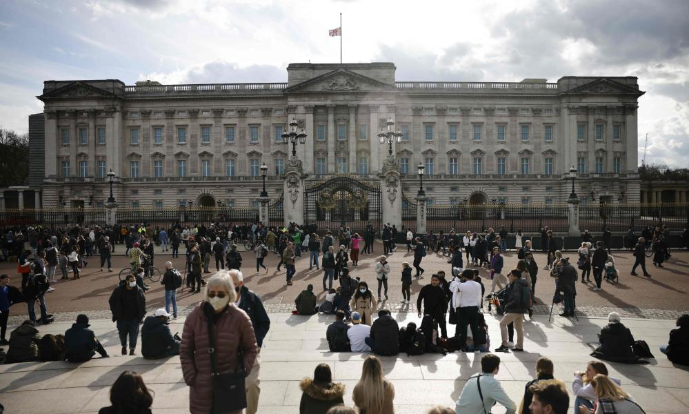People gather outside Buckingham Palace where the union flag flies at half-mast in central London after the announcement of the death of Prince Philip, Duke of Edinburgh.