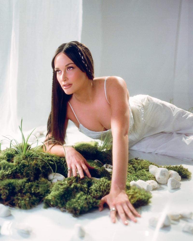 Kacey Musgraves in dress, leaning on moss