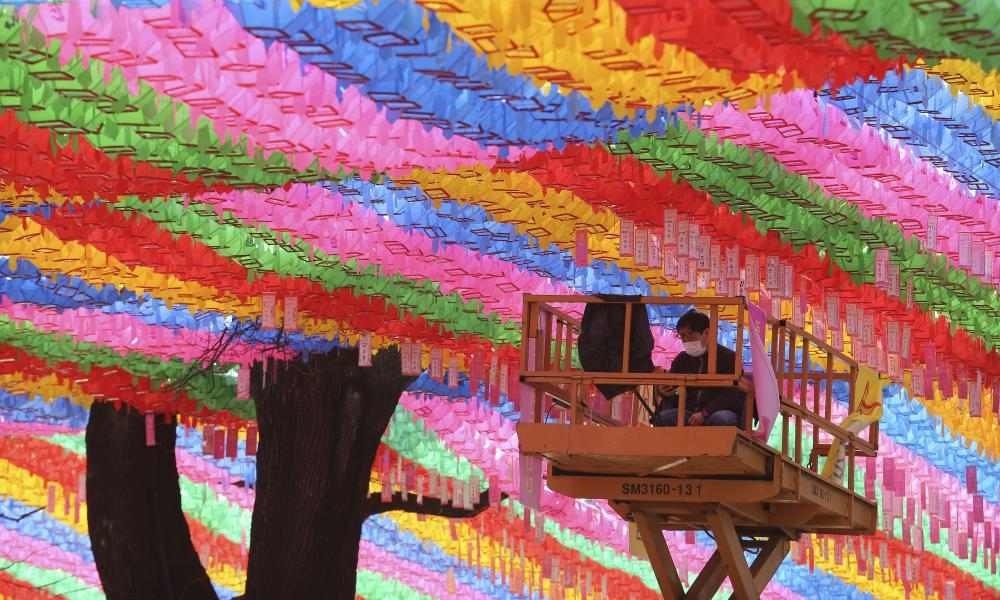 A worker wearing a face mask watches his smart phone under lanterns in preparation for the upcoming birthday of Buddha on April 30 at the Chogyesa temple in Seoul, South Korea, Sunday, March 8, 2020.