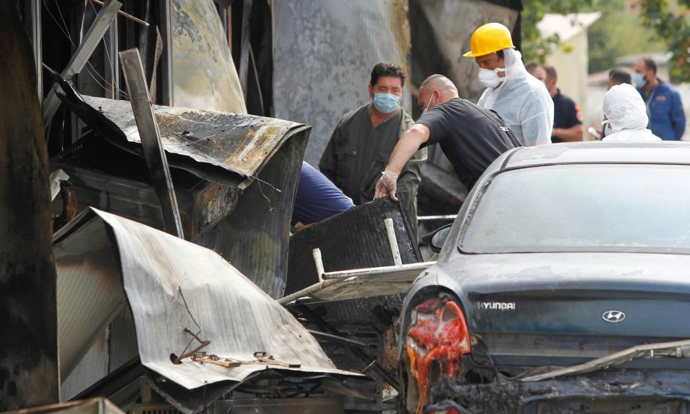 Forensics workers are pictured at the hospital for coronavirus patients in Macedonia following a fire that left 14 dead.
