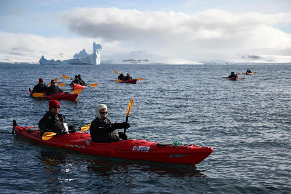 Tourists travel by kayak near Half Moon island, Antarctica.