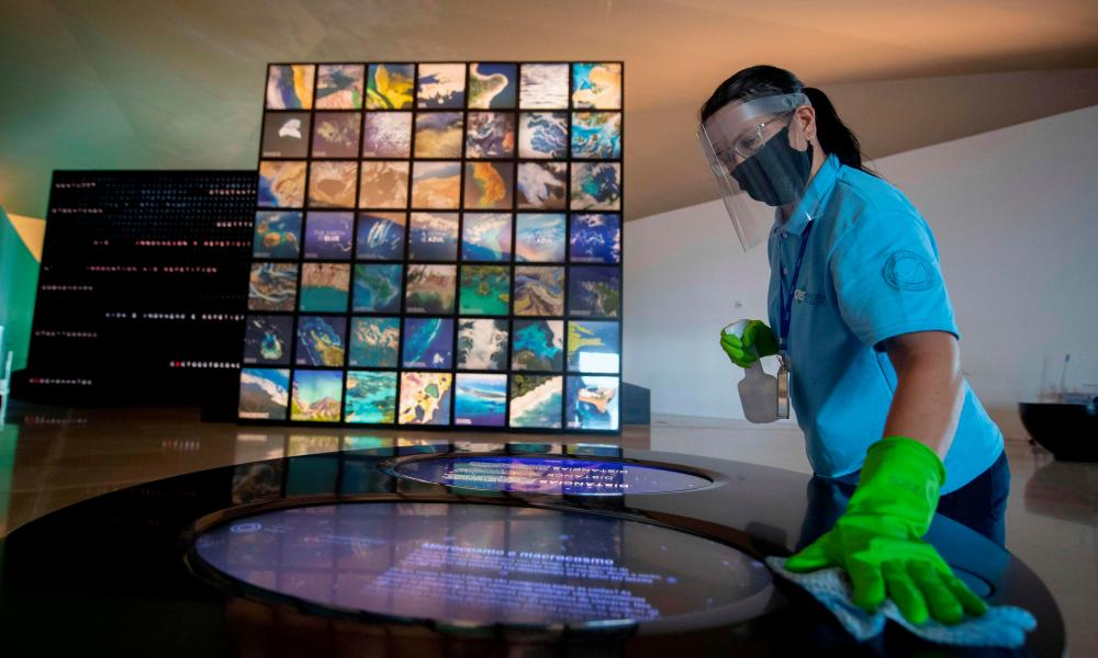 A worker disinfects an area of the Museum of Tomorrow prior to its reopening in Rio de Janeiro, Brazil on Friday amid the COVID-19 novel coronavirus pandemic.