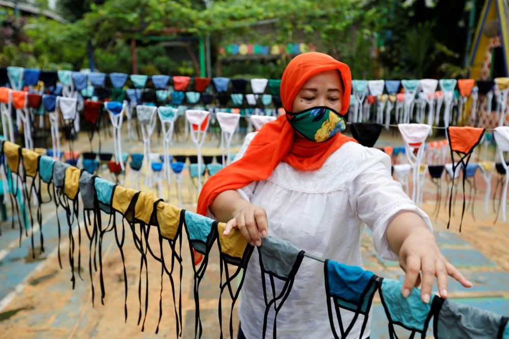 A woman hangs cloth face masks on a string to dry before distributing them around her neighbours in Tangerang, on the outskirts of Jakarta, on Thursday