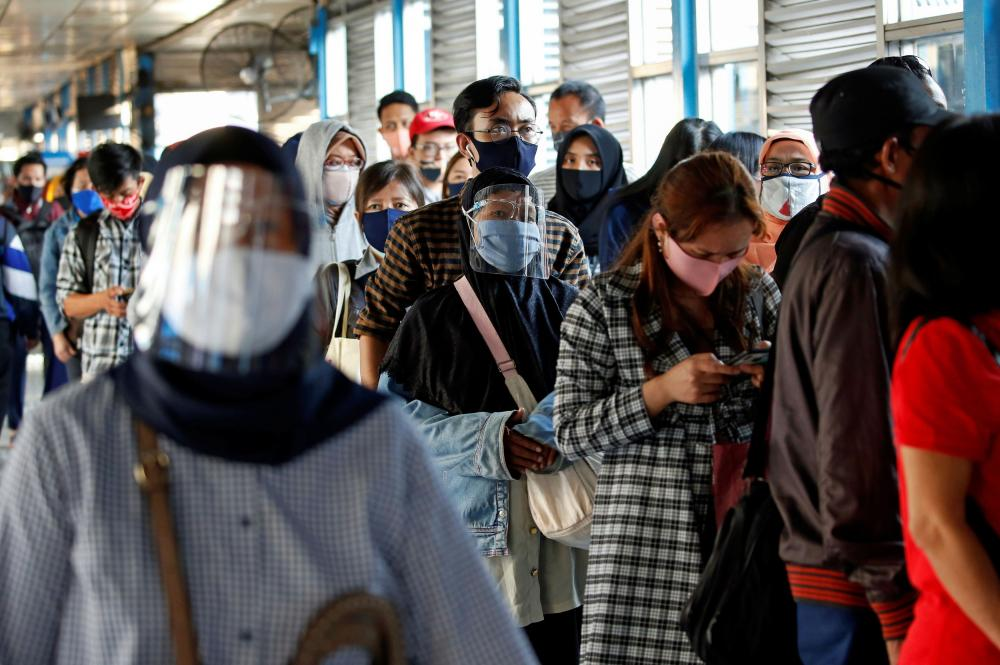 Passengers wearing protective masks and face shields queue for a bus in Jakarta.