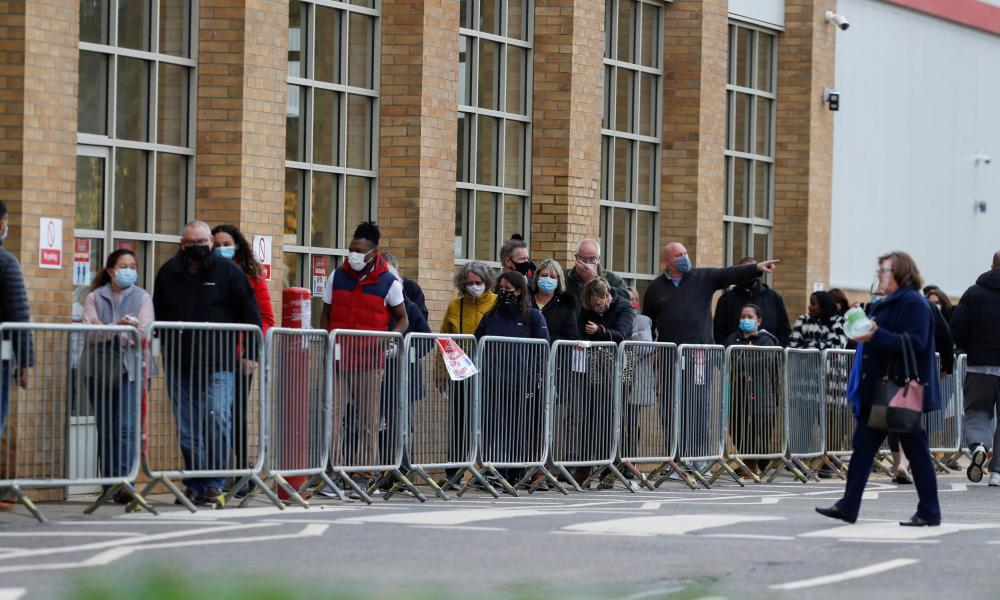 People queuing outside a store in Watford today to buy supplies, ahead of the lockdown starting in England on Thursday.