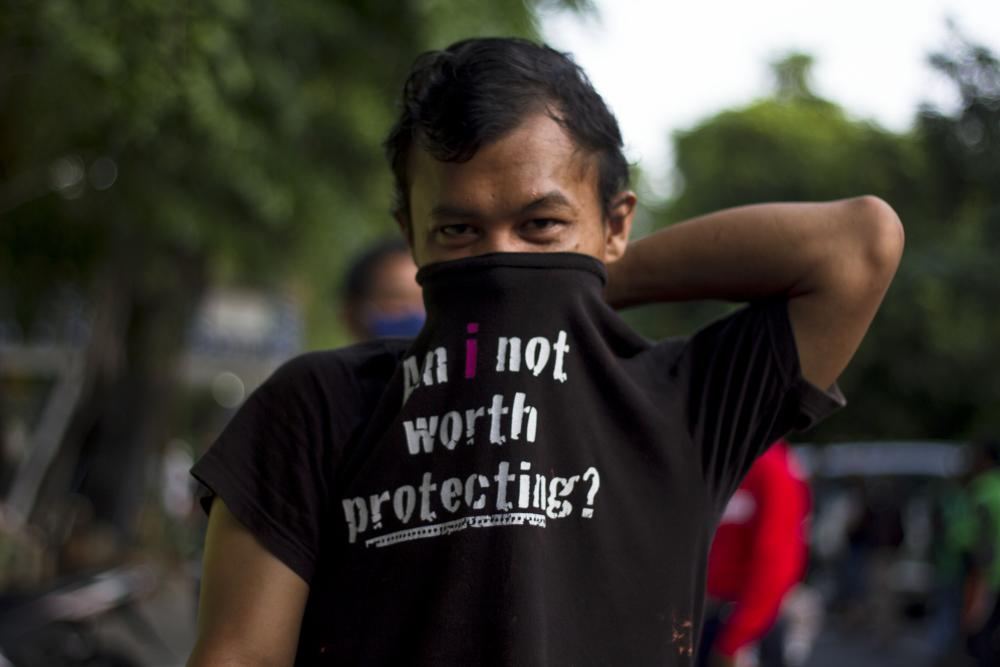 A man covers his face with a shirt instead of a face mask while in a queue to get the Takjil, food for breaking the Ramadan fast, in central Jakarta.
