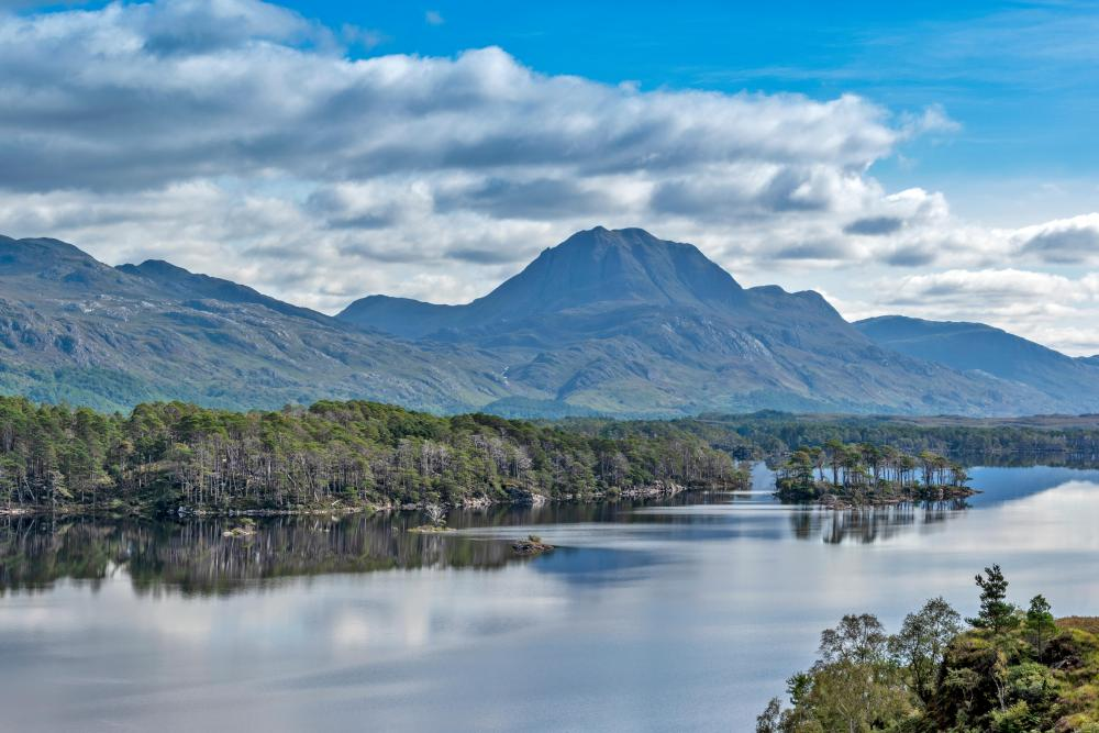 LOCH MAREE, WESTER ROSS, HIGHLANDS, SCOTLAND, LOOKING TOWARDS Slioch WITH THE ISLANDS AND MIRROR CALM WATER.