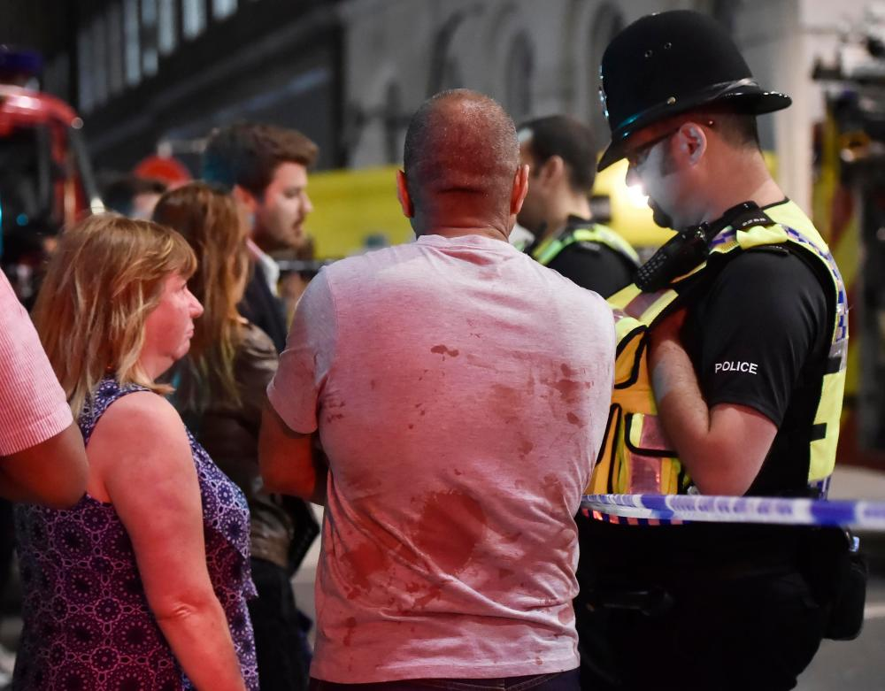 People speak with police officers near London Bridge.