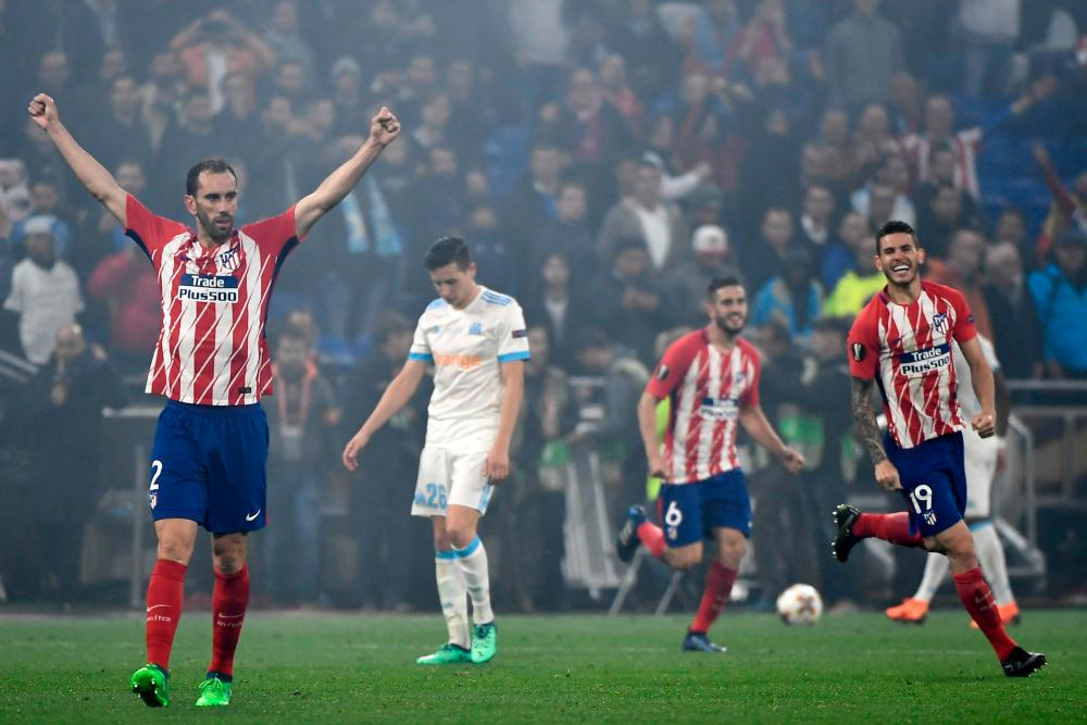 The Atletico's players celebrate as the final whistle goes.