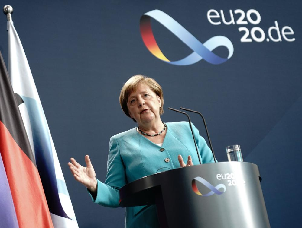 Angela Merkel addresses a joint press conference with EU chief Ursula von der Leyen, joining via video link, at the Chancellery in Berlin.