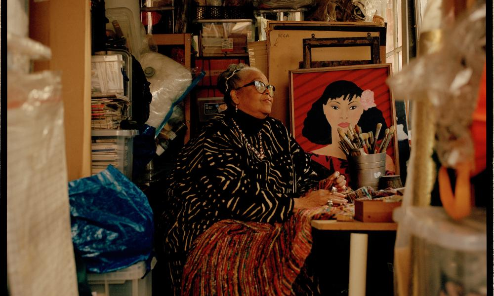 Rita Keegan sitting in a studio with piles of paintings and other materials, inclusdng one portrait of a young woman facing the camera